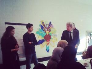 Ismael Jaddi en Sara Zieter bieden burgemeester Van der Laan hun boekje aan
